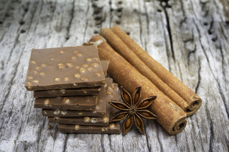 anice: chocolate anice with and cinnamon on old wood background Stock Photo