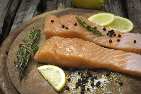 rosmarin: Fresh salmon with spices on old wood background  Stock Photo