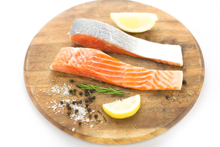rosmarin: Fresh salmon with spices on wood over white background  Stock Photo