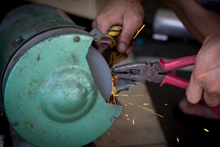 Worker cutting metal with grinder, Sparks while grinding iron  photo