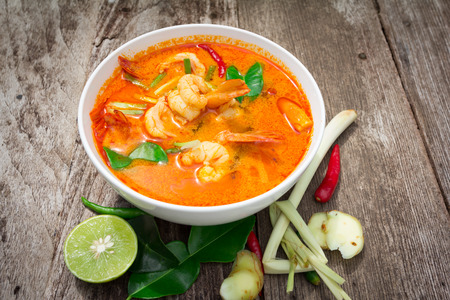 Tom Yam Kung, Spicy Thai food on old wood  Stock Photo