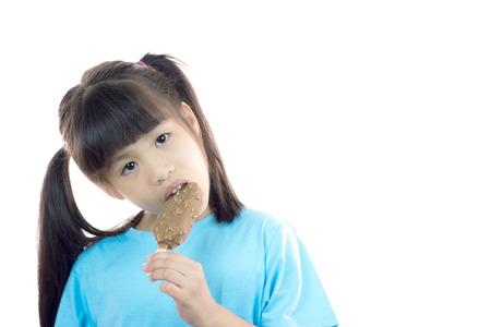 Cute Asian girl eating ice cream in studio isolated photo