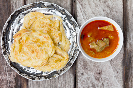roti canai met pittige curry op oud hout, Top View Stockfoto