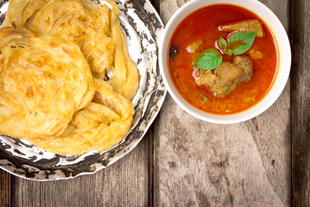 pakistani food: roti canai with spicy curry on old wood, Top view
