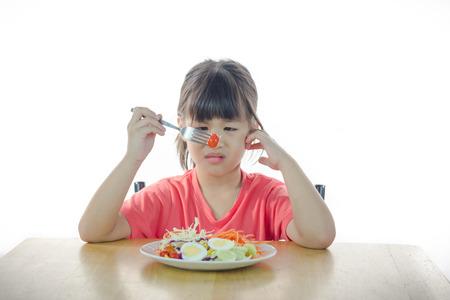 Cute Asian girl refusing to eat vegetable soft focus