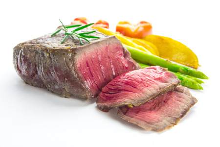 grilled fillet steak served with tomatoes and roast vegetables on white background photo