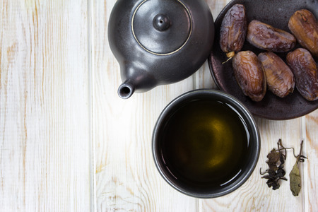 Top view, Dried dates on plate with cup of tea on wood table  photo