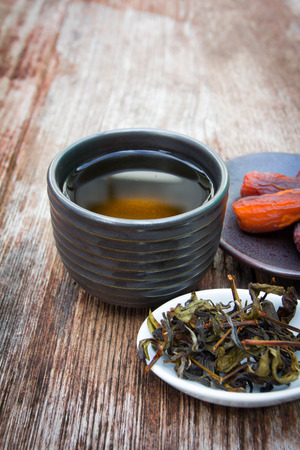 cup of black tea and dates, wooden desk  photo