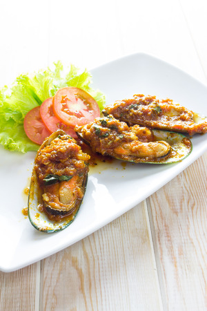 Spicy Fried mussels with tomatoes sauce on wood table photo