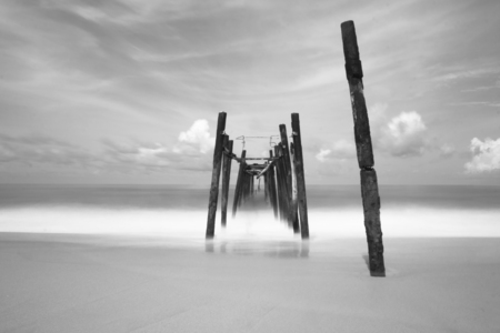 black and white of old bridge to the sea Imagens