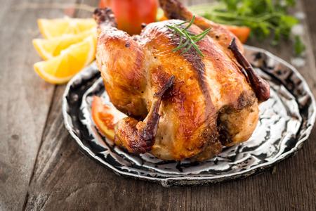 poulet entier rôti sur la vieille table en bois Banque d'images