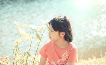 petite fille triste: petite fille triste en arrière-plan de bokeh naturelle