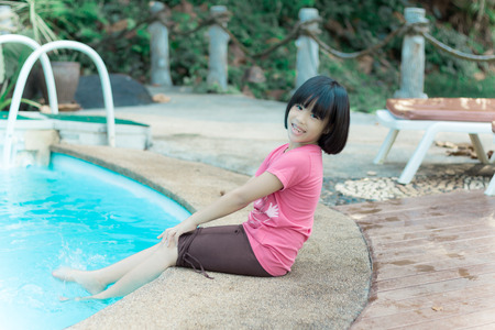 sitting down: Pool woman relaxing sitting in summer dress with legs in pool