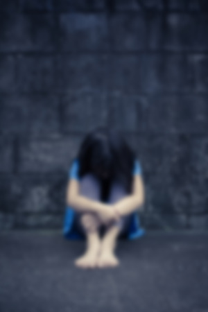 blurr: little girl despair sitting against a brick wall, Motion blurr Stock Photo