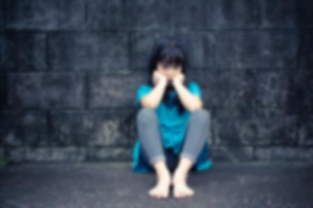 maltrato infantil: poco desesperación chica sentada contra una pared de ladrillo, Movimiento blurr