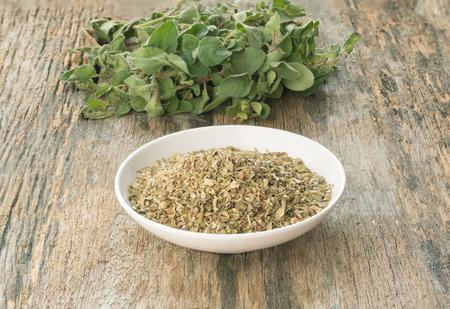 marjoram: Fresh and dried oregano on wood background