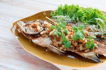 sea bass: Thai style food main course: whole fried sea bass with garlic Stock Photo
