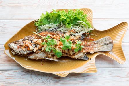 pescado frito: Vista superior, plato principal comida tailandesa de estilo: todo frito lubina con ajo Foto de archivo