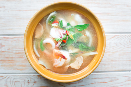 seafood soup: Top view, Thai-spicy soup with seafood on wood table
