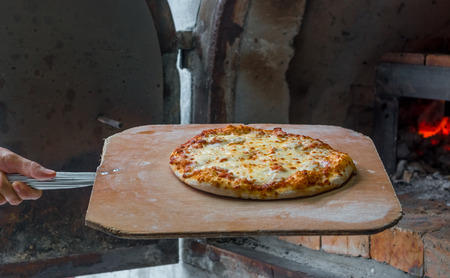 woodfire: Chef Pizza take out of bread oven Stock Photo