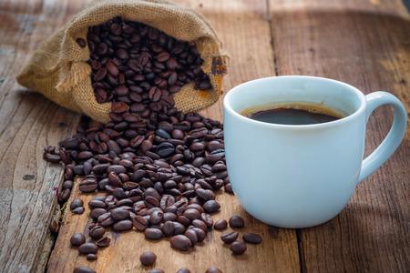 tomando café: Taza de café y granos de café en la madera vieja