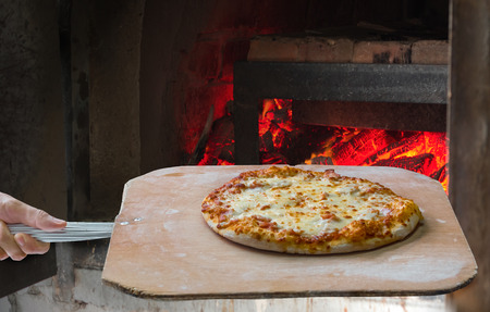 working place: Hand pushing the finished pizza from the oven with the pizza shovel