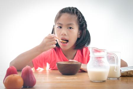 comiendo cereal: Niña asiática linda que come el cereal con la leche en el fondo blanco