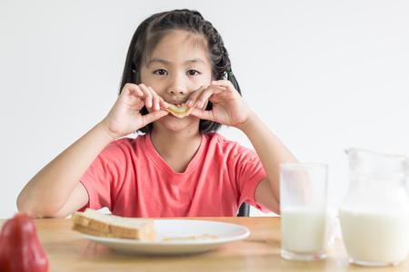 niña comiendo: linda niña asiática que come el emparedado con la leche en la mesa del desayuno
