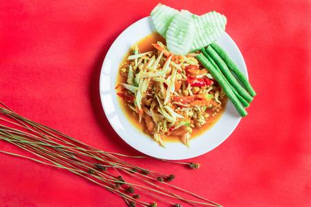 somtum: Famous Thai food, papaya salad on red background