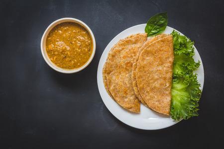 Roti en kip curry. Top weergave op een zwarte achtergrond Stockfoto
