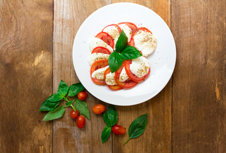 caprese salad: Caprese salad with mozzarella, tomato, basil on white plate. Top view on wood background