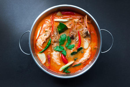 Tom Yum Goong,Thai Food in hot pot, top view on black background Stock Photo