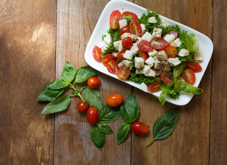 vegetable salad: Caprese salad, Italian salad,Tomato mozzarella basil leaves. Top view on wood background Stock Photo