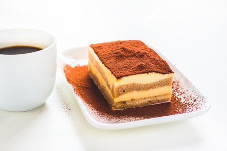Tasty tiramisu cake with coffee cup on white background Stock Photo