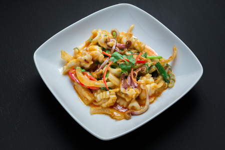 green onion: Stir Fried squid with salted egg york on black background