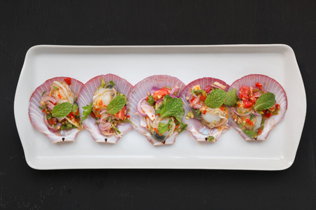 deepsea: Spicy salad with deep-sea scallops in Thai style on black backgound Stock Photo