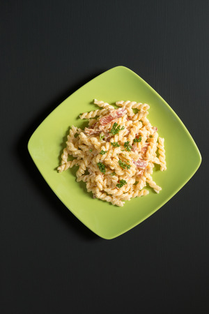 fusilli Pasta Carbonara with ham and cheese on black background Stock Photo