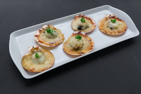 fish plate: Baked parmesan scallops on black background