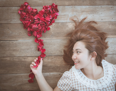 s day: Happy asian girl with red rose heart shape on old wood background, use filter images