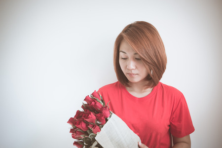 melancholia: Young Asian girl with red roses bouquet, use filter images Stock Photo