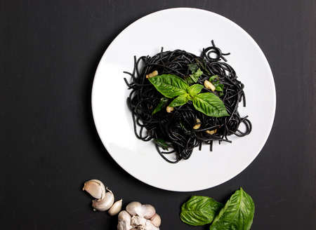 Black spaghetti with olive oil and garlic on black background Imagens