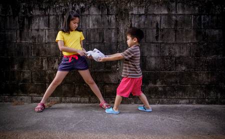 stubbornness: little boy and girls fighting and shared doll
