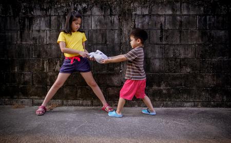 pull toy: niño pequeño y muchachas que luchan y muñeca compartida
