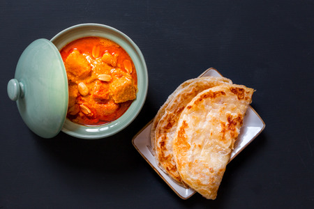 beef curry: Beef massaman curry, thai cuisine eat with roti on black background, top view Stock Photo