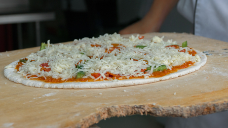 Cheese being spread on tomato sauce on pizza base. Selective focus