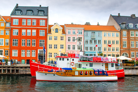 Copenhagen, Denmark - 29 August 2018: Colorful houses and boats on the embankment of the canal in the Nyhavn Editorial