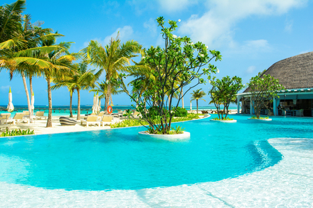 Lhaviyani Atoll, Maldives - 13 July 2018: Pool area on the shores of the Indian Ocean with sunbeds and umbrellas in the shade of the palm trees Editöryel
