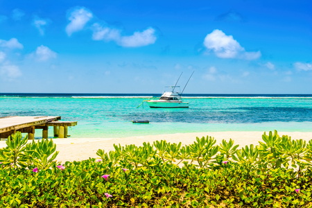 Lhaviyani Atoll, Maldives - 30 July 2018: Boat in the Indian Ocean on the background with a tropical island landscape and a sandy beach