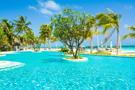 Lhaviyani Atoll, Maldives - 13 July 2018: Pool area on the shores of the Indian Ocean with sunbeds and umbrellas in the shade of the palm trees Standard-Bild - 113681694