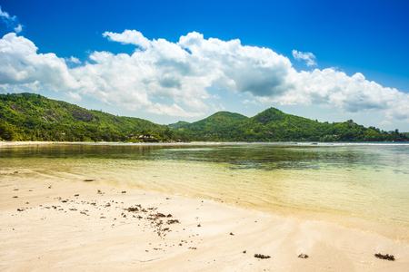 Beautiful tropical landscape of a sandy beach with boulders and green hills, on the shores of the Indian Ocean, Seychelles Standard-Bild - 126089717
